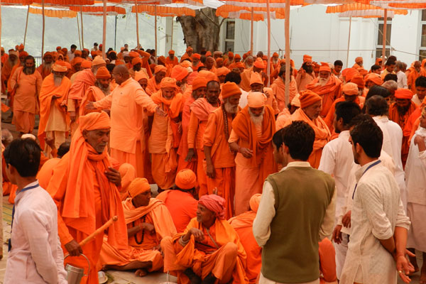 Sadhus being helped to sit for the next Batch