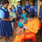 Swamini autographs for a School Girl towards end of the Camp